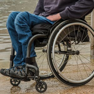 A person wearing jeans and using a wheelchair on the shore of a lake.