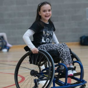 A smiling girl using a wheelchair in a gymnasium